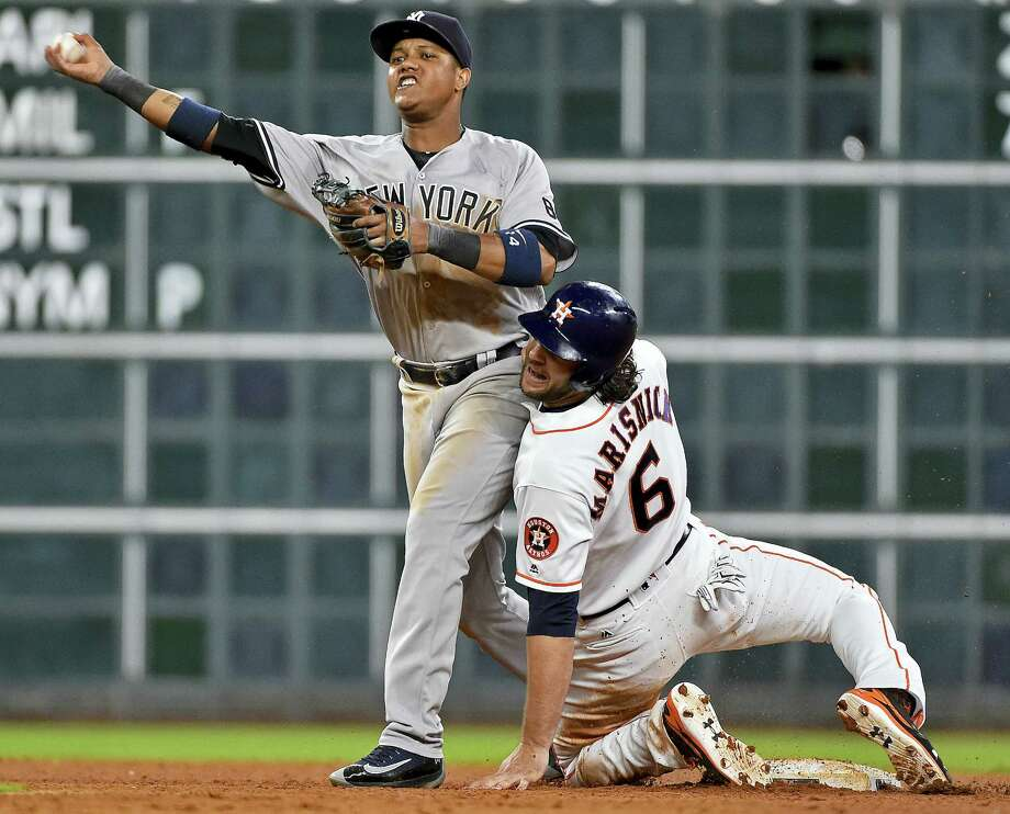 Yankees second baseman Starlin Castro, left, throws to first on an attempted double play against the Astros on Monday. Photo: Eric Christian Smith — The Associated Press  / FR171023 AP