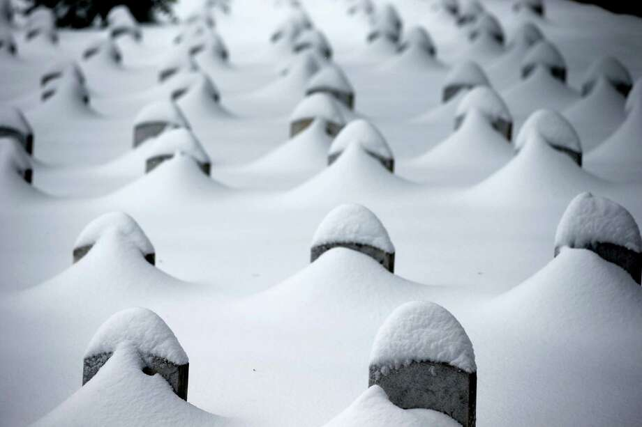 Headstones are nearly covered by snow at Arlington National Cemetery, Saturday, Jan. 23, 2016, in Arlington, Va. A blizzard with hurricane-force winds brought much of the East Coast to a standstill Saturday, dumping as much as 3 feet of snow, stranding tens of thousands of travelers and shutting down the nation's capital and its largest city. Photo: AP Photo/Alex Brandon   / AP