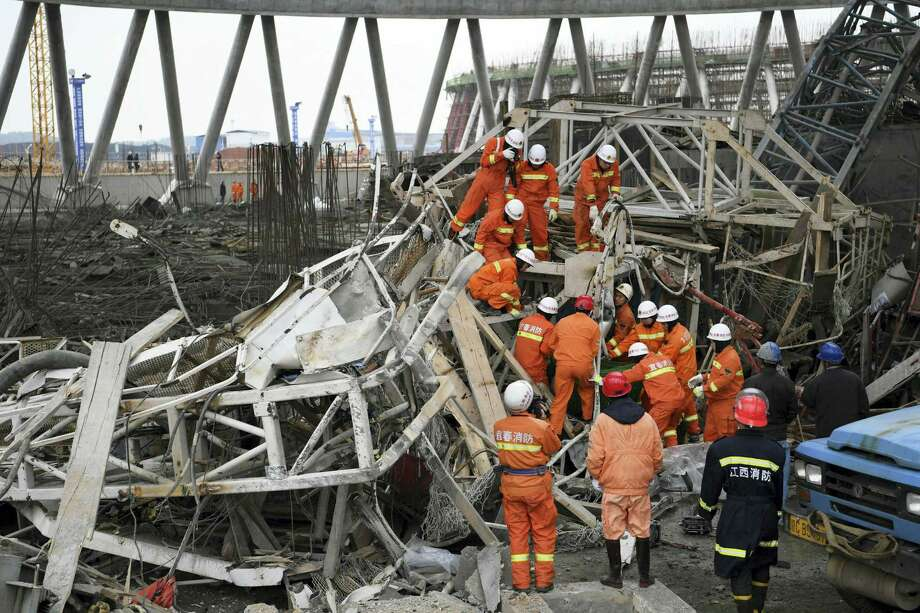 In this photo released by Xinhua News Agency, rescue workers look for survivors after a work platform collapsed at the Fengcheng power plant in eastern China's Jiangxi Province, Nov. 24, 2016. State media reported dozens were killed after the scaffolding tumbled down. Photo: Wan Xiang — Xinhua Via AP / Xinhua