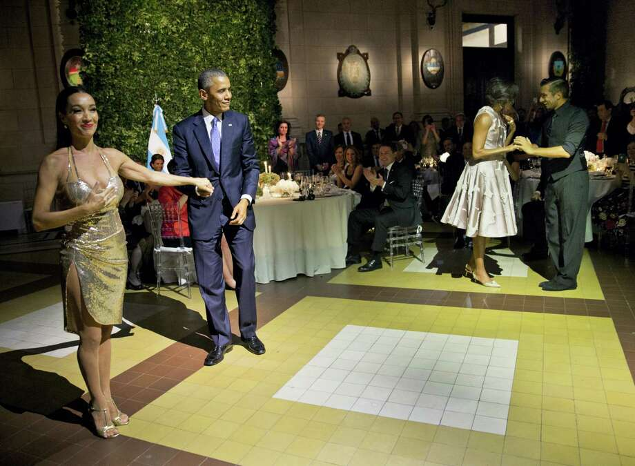 President Barack Obama and first lady Michelle Obama stand with tango dancers after dancing the tango during the State Dinner at the Centro Cultural Kirchner on March 23, 2016 in Buenos Aires, Argentina. Photo: AP Photo/Pablo Martinez Monsivais  / AP
