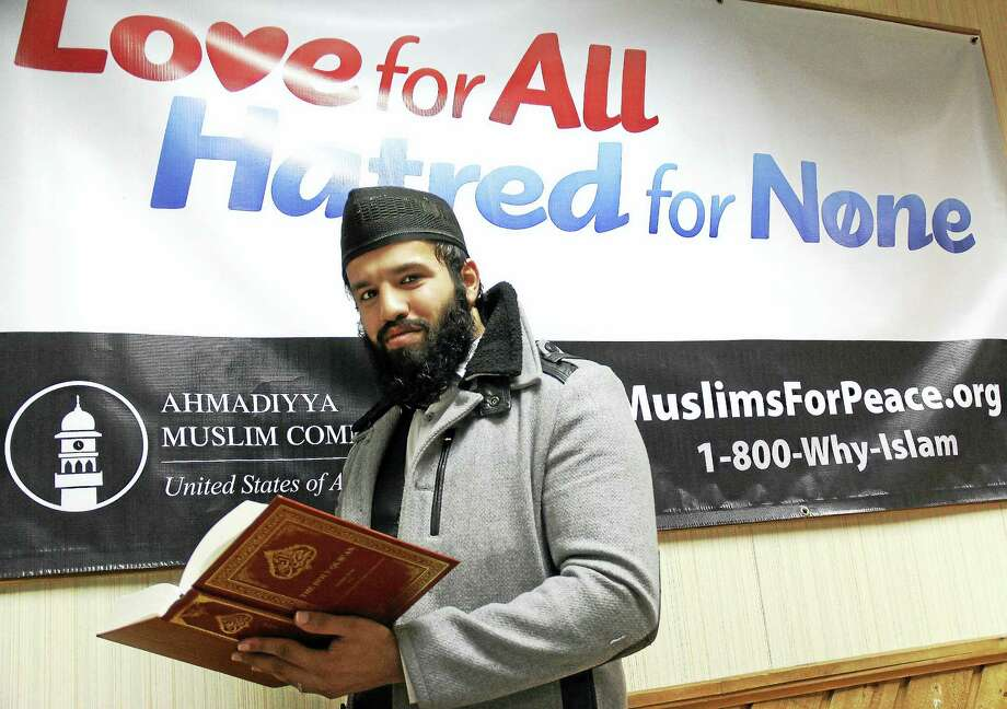 "Middletown resident Miyan Zahir Muhammad Manna, mosque outreach director, holds the Holy Quran at the Baitul Aman ""House of Peace"" mosque, based in Meriden, for the statewide chapter of the Ahmadiyya Muslim Community. Photo: Kathleen Schassler — The Middletown Press  / Kathleen Schassler All Rights"