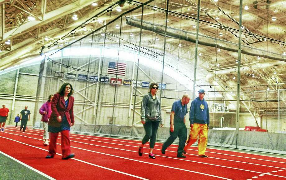 Team Gilead members walk at the indoor track at Wesleyan Univesity as they train for the Middletown Half & Legends 4-mile Road Race. Photo: Kathleen Schassler — The Middletown Press