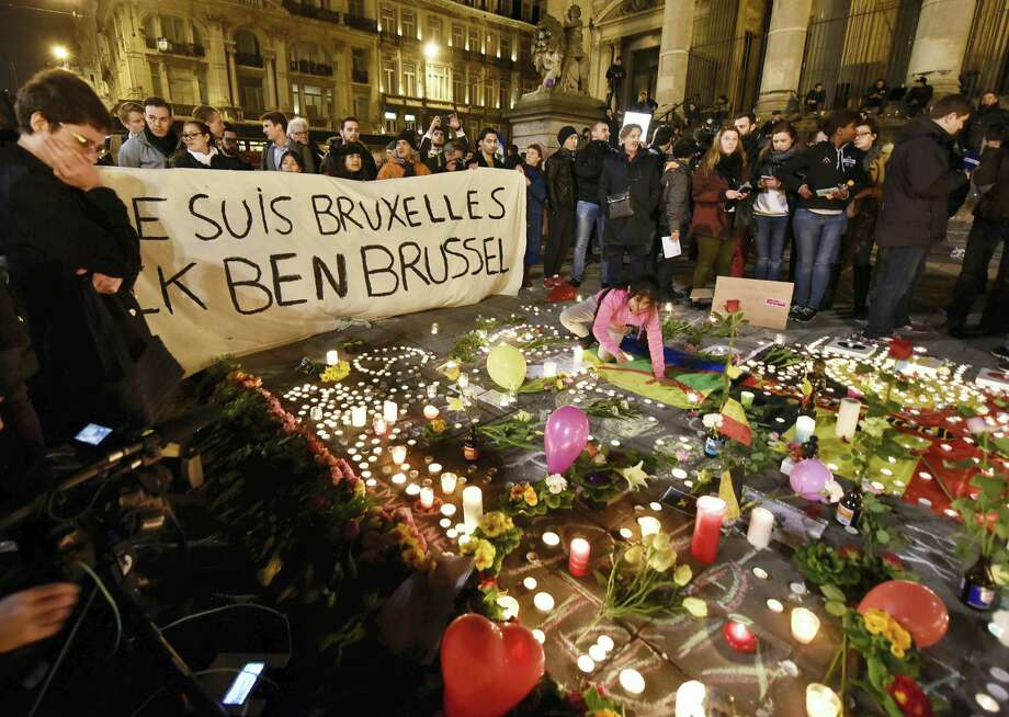 "People holding a banner reading ""I am Brussels"" behind flowers and candles to mourn for the victims at Place de la Bourse in the center of Brussels, Tuesday, March 22, 2016. Bombs exploded at the Brussels airport and one of the city's metro stations Tuesday, killing and wounding scores of people, as a European capital was again locked down amid heightened security threats. Photo: AP Photo/Martin Meissner / AP"