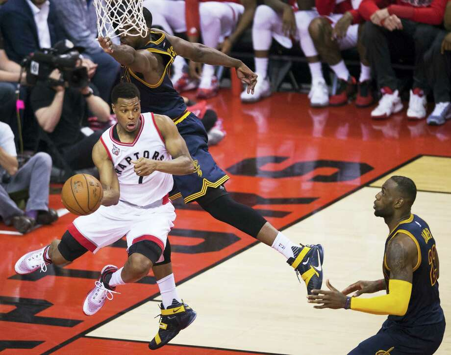 Raptors guard Kyle Lowry (7) drives around Cavaliers center Tristan Thompson as LeBron James looks on during the first half on Monday. Photo: Nathan Denette — The Canadian Press Via AP  / The Canadian Press
