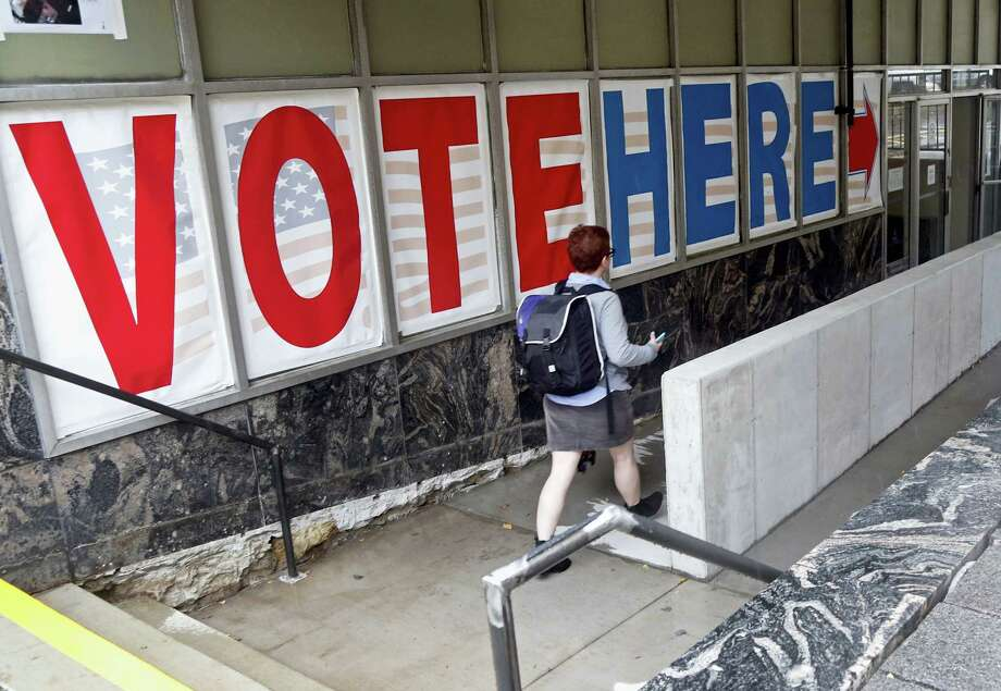 A woman passes a large sign as she arrives to vote Friday in Minneapolis. Election Day is more than a month away, but the voting was already underway Friday, as Minnesota kicked off its first presidential cycle where all voters across the state can cast their ballots early. Photo: The Associated Press  / Copyright 2016 The Associated Press. All rights reserved.