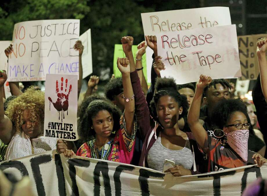 Protesters raises their fists as they march in the streets of Charlotte, N.C. Friday, Sept. 23, 2016, over Tuesday's fatal police shooting of Keith Lamont Scott. Photo: Chuck Burton — The Associated Press  / Copyright 2016 The Associated Press. All rights reserved.