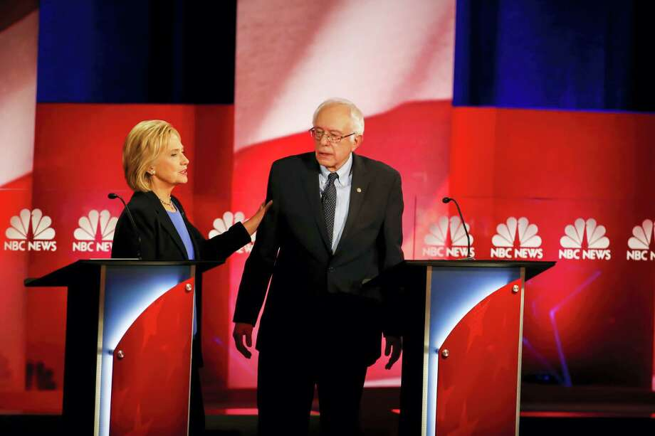 Democratic presidential candidates Hillary Clinton and Sen. Bernie Sanders, I-Vermont, speak during a break at the NBC-YouTube Democratic presidential debate at the Gaillard Center Sunday in Charleston, South Carolina. Photo: THE ASSOCIATED PRESS  / FR56856 AP