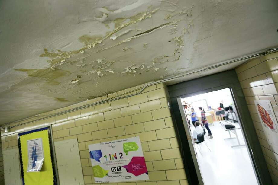 In this photo taken Thursday, Jan. 14, 2016, peeling paint and plaster, damaged from a now fixed leaky roof, dangle above a hallway at Osborn Collegiate Academy of Mathematics Science and Technology in Detroit. Long-awaited legislation to overhaul Detroit's troubled school district by splitting it in two was introduced Thursday and could commit state lawmakers to spending up to $770 million over 11 years on the restructuring proposal that faces uncertainty in a bailout-averse Legislature. Photo: Romain Blanquart/Detroit Free Press Via AP  / Detroit Free Press
