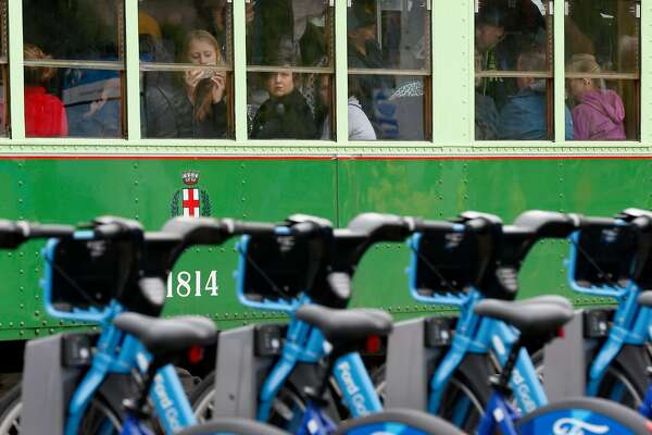 Passengers aboard a crowded Muni streetcar watch the opening festivities for a Ford GoBike bike share station in front of the Ferry Building in San Francisco, Calif. on Wednesday, June 28, 2017. The Bay Area-wide bike sharing service, which plans a fleet of 3,500 bicycles by Labor Day and as many as 7,000 by the end of 2018, went into service today.