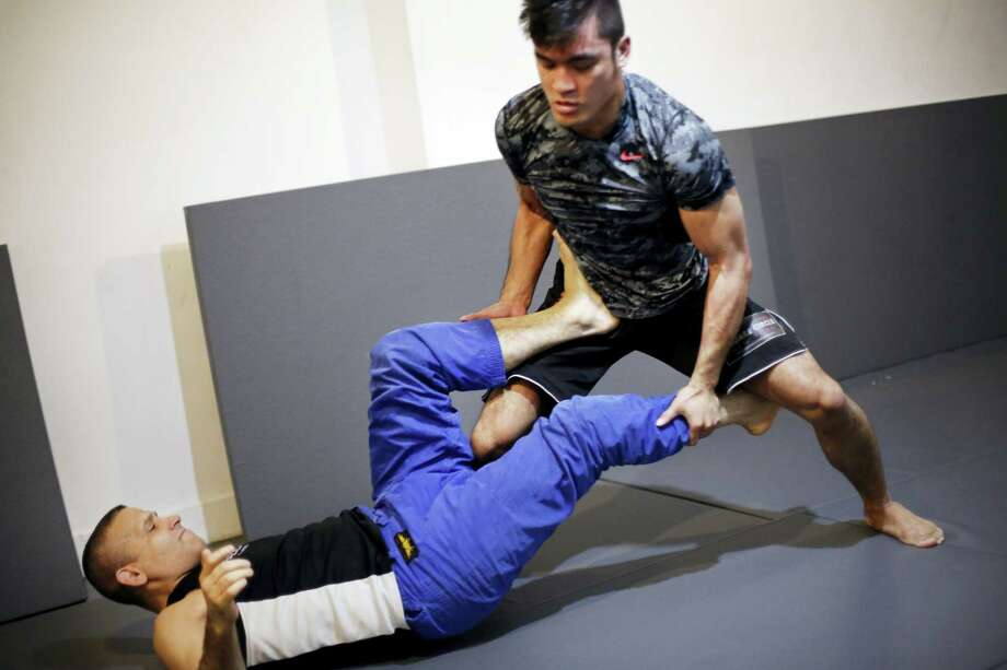 Rene Dreifuss, left, a mixed martial arts coach, trains Richard Callado at Radical MMA NYC, a New York gym, on Tuesday. New York is poised to end its ban on professional mixed martial arts, the last state to prohibit the combat sport. Photo: Mark Lennihan — The Associated Press   / AP