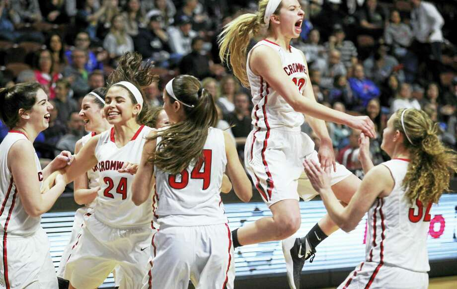 Cromwell's girls basketball team celebrates winning the Class M state title Saturday at the Mohegan Sun Arena. Photo: Photo By Laura Matesky