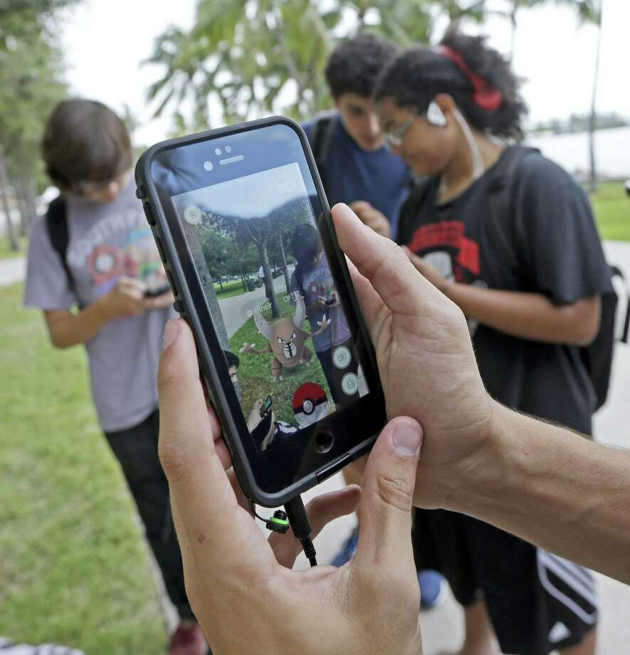 """Pinsir, a Pokemon, is found by a group of Pokemon Go players July 12 in downtown Miami. The Pokemon Go craze has sent legions of players hiking around cities and battling with """"pocket monsters"""" on their smartphones. Photo: AP Photo — Alan Diaz   / Copyright 2016 The Associated Press. All rights reserved. This material may not be published, broadcast, rewritten or redistribu"""