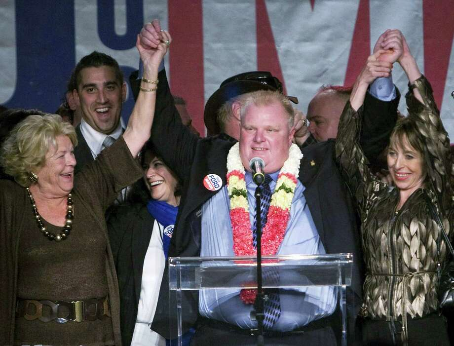 In this Oct. 25, 2010, file photo, Toronto Mayor-elect Rob Ford, center raises his arms with his wife Renata, right, and mother Diane, left, as he speaks to supporters in Toronto. Ford, whose career crashed in a drug-driven, obscenity-laced debacle, died Tuesday, March 22, 2016, after fighting cancer, his family says. He was 46. Photo: Nathan Denette/The Canadian Press Via AP   / The Canadian Press