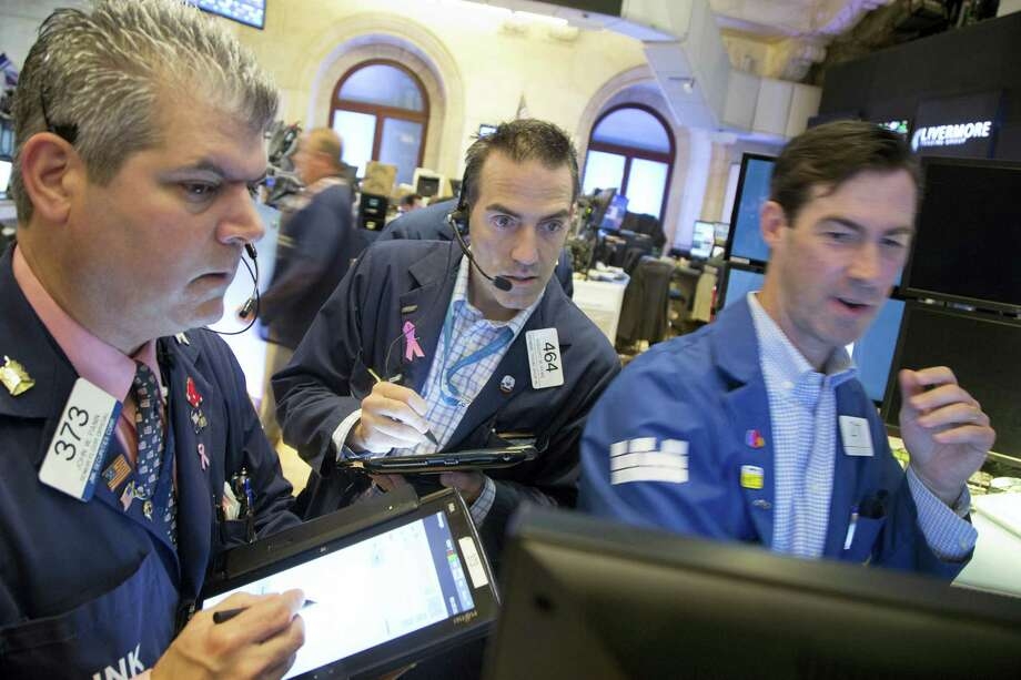 John McNierney, right, trading GE stock for Citadel Securities, updates John Panin, left, and Greg Rowe, center, with the stock's price at the New York Stock Exchange Friday. Photo: Mark Lennihan — The Associated Press  / Copyright 2016 The Associated Press. All rights reserved. This material may not be published, broadcast, rewritten or redistribu