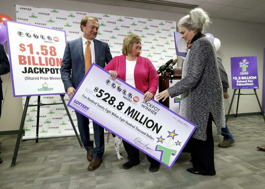 Lisa Robinson, center, carries a ceremonial check as she leaves a news conference with Rebecca Hargrove, right, president and CEO of the Tennessee Lottery, and attorney Joe Townsend, left, Friday, Jan. 15, 2016, in Nashville, Tenn. The Robinsons' winning Powerball ticket is one of three winning tickets in the $1.6 billion jackpot drawing held Wednesday. Photo: AP Photo/Mark Humphrey   / AP