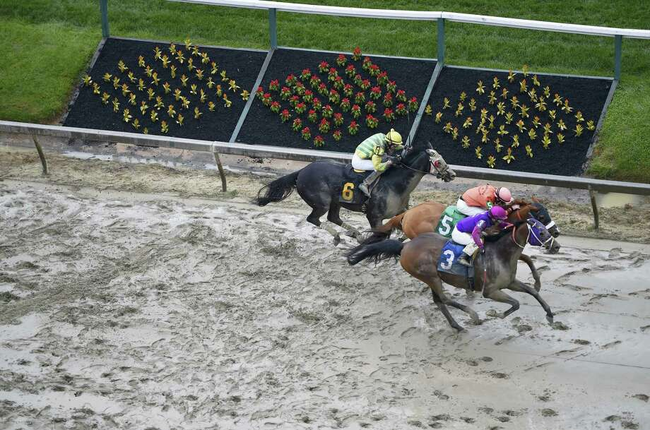 Homeboykris (3), ridden by Horacio Karamanos, wins the first race of the day on a muddy track ahead of the 141st Preakness Stakes on Saturday. After the race, Homeboykris collapsed and died after having his picture taken in the winner's circle. Photo: Mike Stewart — The Associated Press  / AP