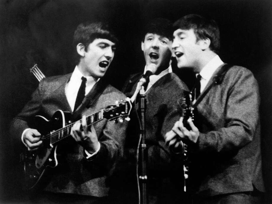 George Harrison, left, Paul McCartney, center and John Lennon, right, three members of the Beatles group during a concert, in London, on Nov. 11, 1963. Photo: AP Photo  / AP1963