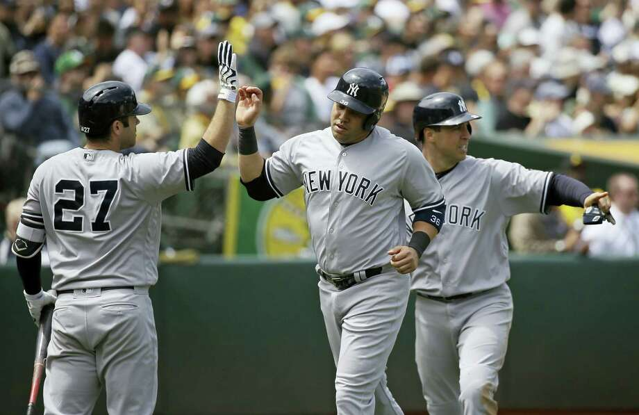 Carlos Beltran, center, and Mark Teixeira, right, are greeted by Austin Romine, left, after scoring in the fourth inning on Sarturday. Photo: Eric Risberg — The Associated Press  / Copyright 2016 The Associated Press. All rights reserved. This material may not be published, broadcast, rewritten or redistribu