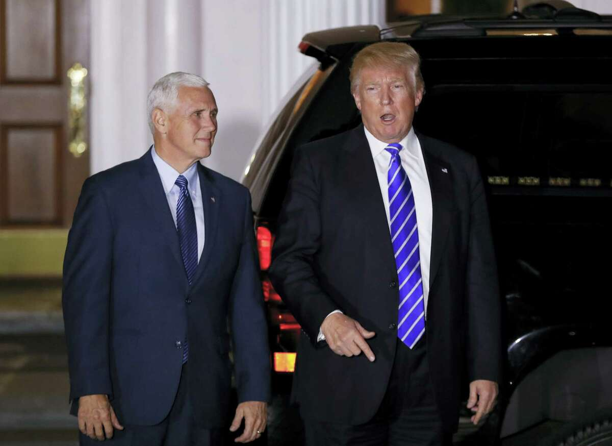 President-elect Donald Trump pauses to talk to media as he walks with Vice President-elect Mike Pence to board his motorcade vehicle at Trump National Golf Club Bedminster clubhouse in Bedminster, N.J. on Nov. 19, 2016 to go back to his residence on the grounds for a break in meetings.