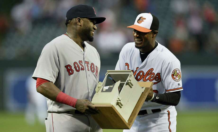 The Orioles' Adam Jones, right, presents David Ortiz with a dugout phone, which Ortiz smashed during the 2013 season after striking out, during a ceremony before Thursday's game. Photo: Gail Burton — The Associated Press  / FR4095 AP