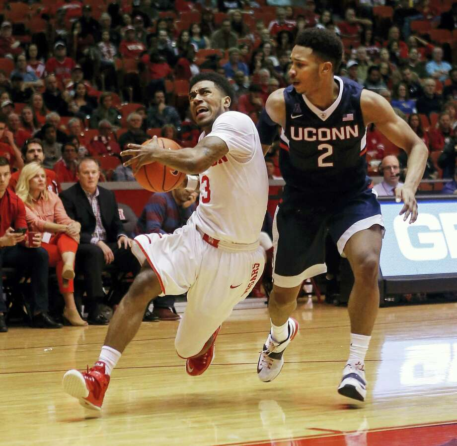 UConn's Jalen Adams, right, defends Houston guard Ronnie Johnson during Sunday's game. Adams was inserted into the starting lineup by coach Kevin Ollie. Photo: The Associated Press File Photo  / FR156786 AP