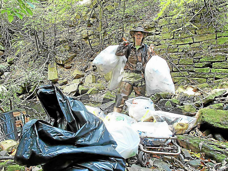 Wesleyan University Professor Elise Springer hauls trash out of a ravine during a past Source to Sea Cleanup in Middletown. Photo: File Photo