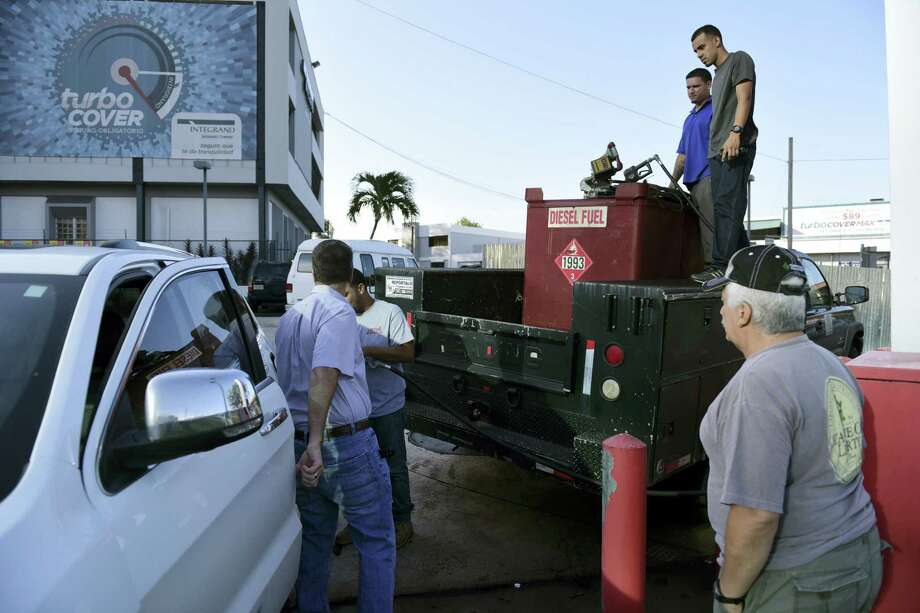 Department of Education employees fill a generator with diesel in San Juan, Puerto Rico, Thursday, Sept. 22, 2016, after a massive blackout hit Puerto Rico Wednesday afternoon, leaving at least 1.5 million people without power overnight and into the following day. Photo: AP Photo/Carlos Giusti   / Copyright 2016 The Associated Press. All rights reserved.