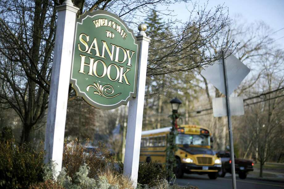 In this Dec. 4, 2013, file photo, a school bus drives past a lamppost decorated for the holidays, and a sign reading Welcome to Sandy Hook, in Newtown, Conn. With winter on their doorstep once again, the people of Newtown are bracing for the day everyone there simply calls 12/14 — referring to the day in 2012 with 26 people were killed by a gunman inside Sandy Hook Elementary School. Photo: AP Photo/Jessica Hill, File   / FR125654 AP