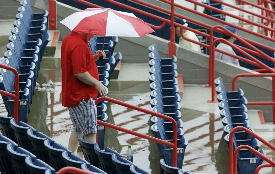 A fan exits a spring training game between the Nationals and Mets after it was cancelled because of rain on Saturday in Viera, Fla. Photo: John Roax — The Associated Press  / Copyright 2016 The Associated Press. All rights reserved. This material may not be published, broadcast, rewritten or redistributed without permission.