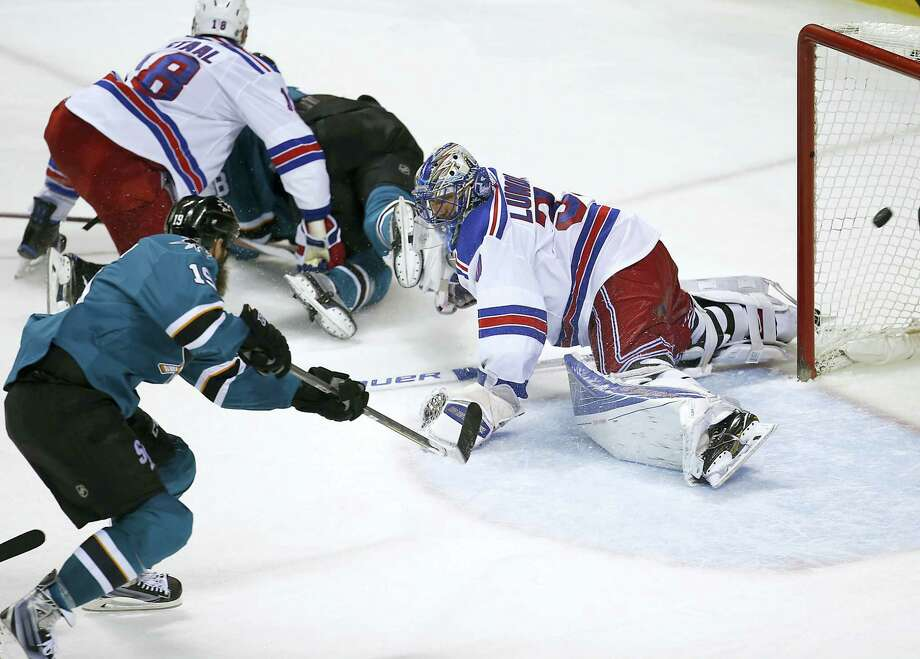 Sharks center Joe Thornton (19) scores a goal past Rangers goalie Henrik Lundqvist during the third period Saturday. Photo: Tony Avelar — The Associated Press  / FR155217 AP