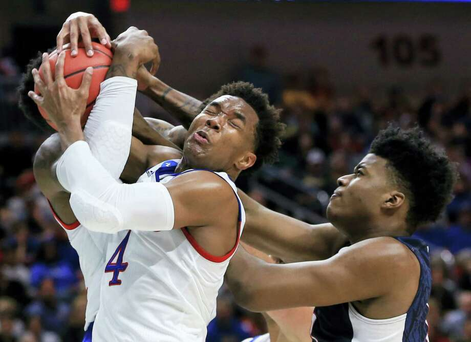UConn's Steven Enoch, right, loses a rebound to Kansas' Wayne Selden Jr. (1), and Jamari Traylor, left rear, during Saturday's second-round game in Des Moines, Iowa. Photo: Nati Harnik — The Associated Press  / Copyright 2016 The Associated Press. All rights reserved. This material may not be published, broadcast, rewritten or redistributed without permission.