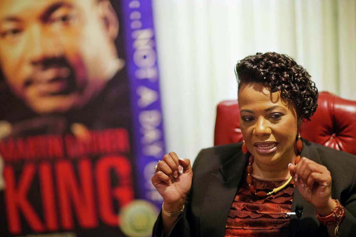 In this Jan. 8, 2016 photo, Bernice King, daughter of Martin Luther King Jr., speaks during an interview in front of an image of her father at the King Center in Atlanta. Marking the 30th anniversary of the Martin Luther King Jr. holiday, the King Center is focusing on the civil rights icon's call for freedom, his daughter Bernice King said.