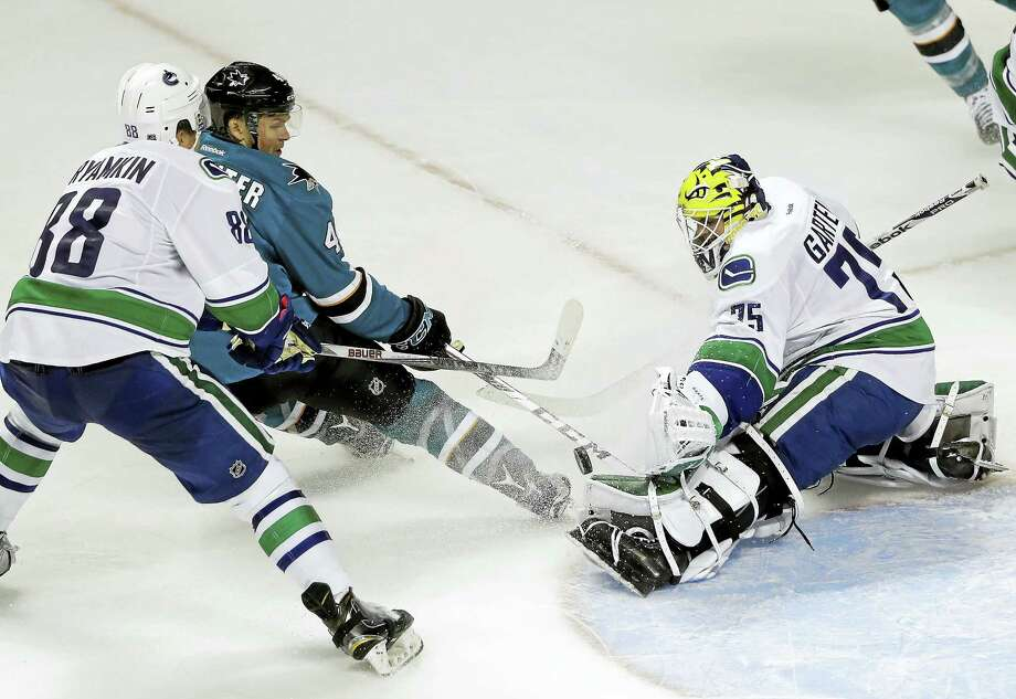 Goalie Michael Garteig, right, deflects a shot for the Vancouver Canucks during a preseason game in September. Photo: The Associated Press File Photo  / AP
