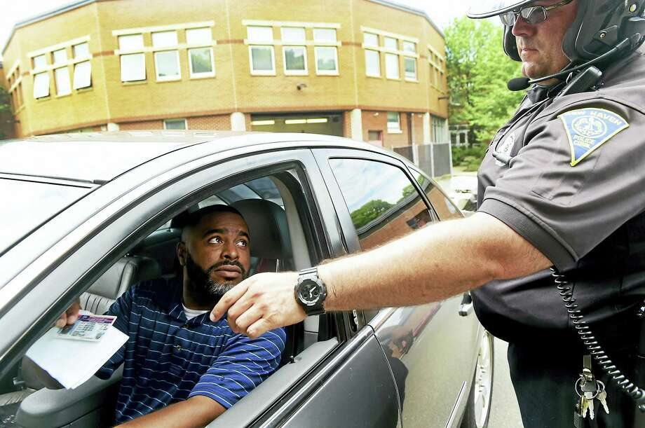 New Haven Police Traffic Police Motorcycle Unit Officer Robert Dupont simulates a traffic stop with New Haven Register Community Engagement Editor Shahid Abdul-Karim. Photo: Peter Hvizdak — New Haven Register  / ©2016 Peter Hvizdak