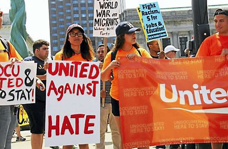 "Yenimar Cortes of New Haven holds a ""United Against Hate"" sign during an anti-Trump rally in downtown Cleveland. Photo: Dillon Carr, RichlandSource For CTNewsJunkie"