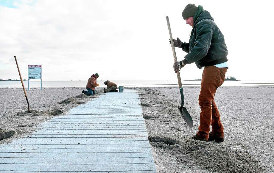 Ryan Maher, right, a seasonal maintenance worker with the Parks Division of the Connecticut DEEP, and coworkers remove a handicapped ramp on the beach at Silver Sands State Park in Milford. Photo: Arnold Gold — New Haven Register FILE PHOTO
