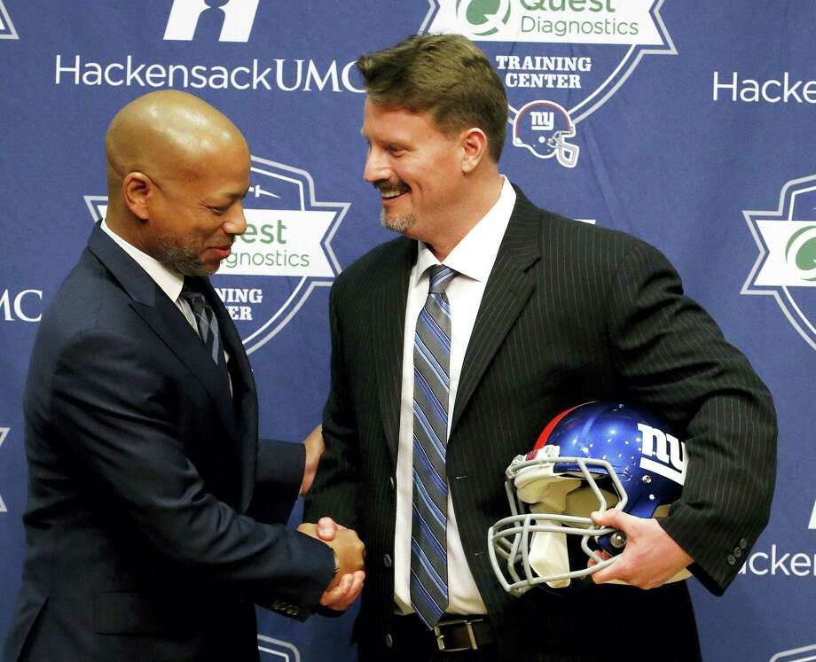 Giants general manager Jerry Reese, left, shakes hands with new head coach Ben McAdoo during a news conference on Friday. Photo: Julio Cortez — The Associated Press  / AP