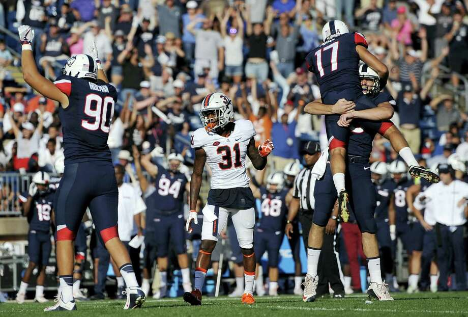 UConn placekicker Bobby Puyol, top, celebrates his game-winning field goal with Tyler Davis (9) beside Virginia's Kareem Gibson (31) in the second half Saturday. The Huskies won 13-10. Photo: JESSICA HILL — THE ASSOCIATED PRESS  / FR125654 AP