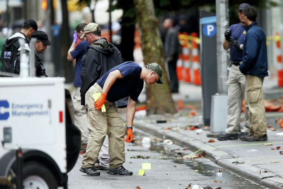 Evidence teams investigate at the scene of an explosion on West 23 Street in Manhattan's Chelsea neighborhood Sept. 19 in New York. Photo: AP Photo — Jason DeCrow   / FR103966 AP