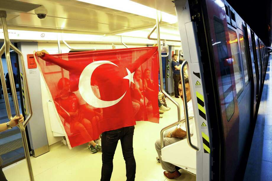 A Turkish man holds a Turkish  flag as he stands inside a metro carriage at Kizilay metro station, in Ankara, Turkey on July 18, 2016. Warplanes patrolled Turkey's skies overnight in a sign that authorities feared that the threat against President Recep Tayyip Erdogan's government was not yet over, despite official assurances that life has returned to normal after a failed coup. Photo: AP Photo/Hussein Malla  / Copyright 2016 The Associated Press. All rights reserved. This material may not be published, broadcast, rewritten or redistribu