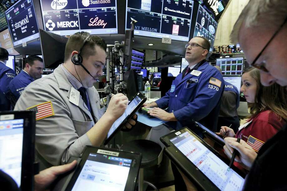 Traders gather at the post of Anthony Matesic, background right, on the floor of the New York Stock Exchange Friday. Photo: Richard Drew — The Associated Press  / Copyright 2016 The Associated Press. All rights reserved. This material may not be published, broadcast, rewritten or redistributed without permission.