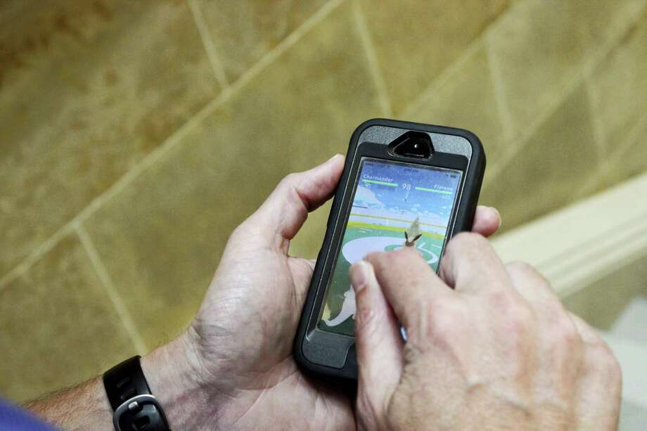 "Associated Press reporter Todd Richmond uses Charmander to battle Flareon in ""Pokemon Go"" in the Wisconsin state Capitol in Madison. Photo: THE ASSOCIATED PRESS  / Copyright 2016 The Associated Press. All rights reserved. This material may not be published, broadcast, rewritten or redistribu"