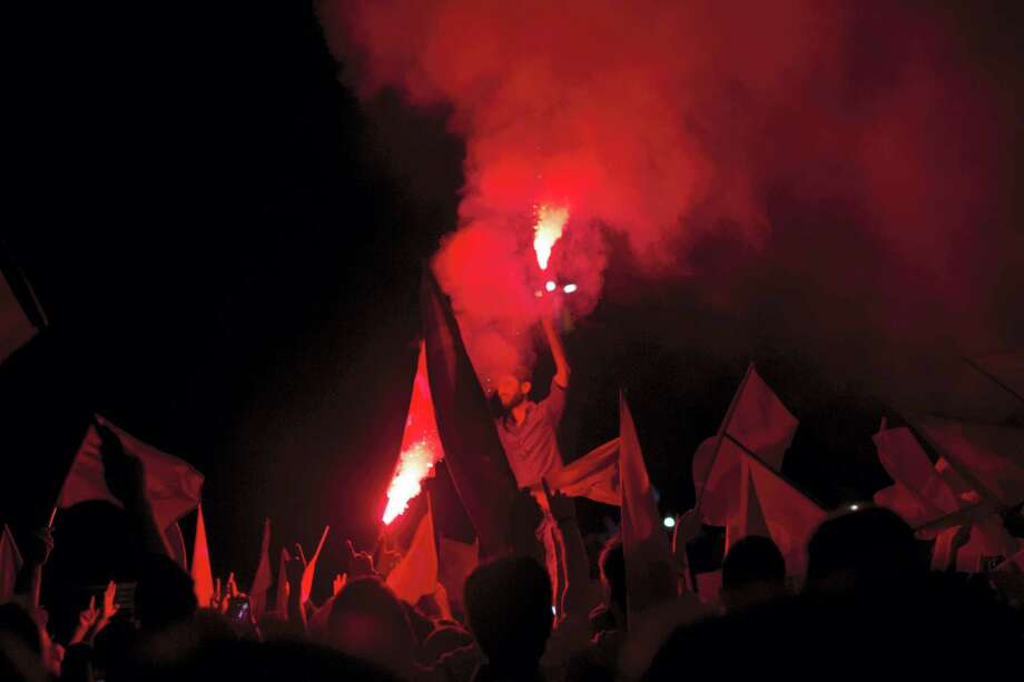 Government supporters light flares during a protest in Taksim Square, in Istanbul, Monday. Turkey's Interior Ministry has fired nearly 9,000 police officers, bureaucrats and others and detained thousands of suspected plotters following a foiled coup against the government, Turkey's state-run news agency reported Monday. Photo: THE ASSOCIATED PRESS  / Copyright 2016 The Associated Press. All rights reserved. This material may not be published, broadcast, rewritten or redistribu