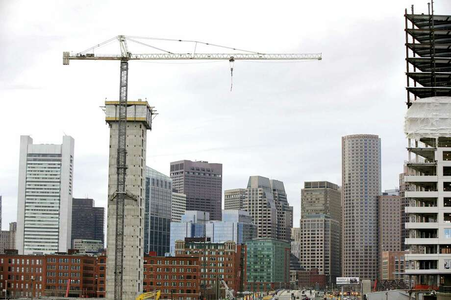 In this April 4, 2014, file photo, several commercial construction projects take place in Boston's Seaport District against the backdrop of the city's skyline. General Electric said Wednesday, Jan. 13, 2016, it will begin relocating its global headquarters to the district in the summer from Fairfield, Conn., and complete the move by 2018. Boston's Seaport District long was filled with docks, warehouses and parking lots. But in recent years it has become the city's hottest and fastest-growing neighborhood. Photo: AP Photo/Stephan Savoia, File   / AP
