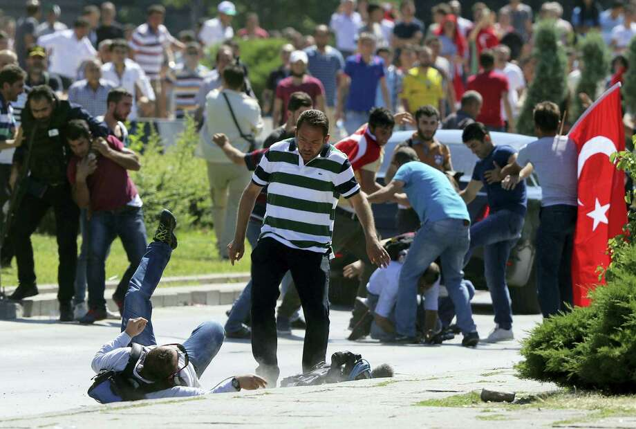 Supporters of Turkey's President Recep Tayyip Erdogan, who were staging a protest against a coup, clash with Turkish journalists near the Turkish military headquarters, in Ankara, Turkey, Saturday. Photo: Associated Press  / Copyright 2016 The Associated Press. All rights reserved. This material may not be published, broadcast, rewritten or redistribu