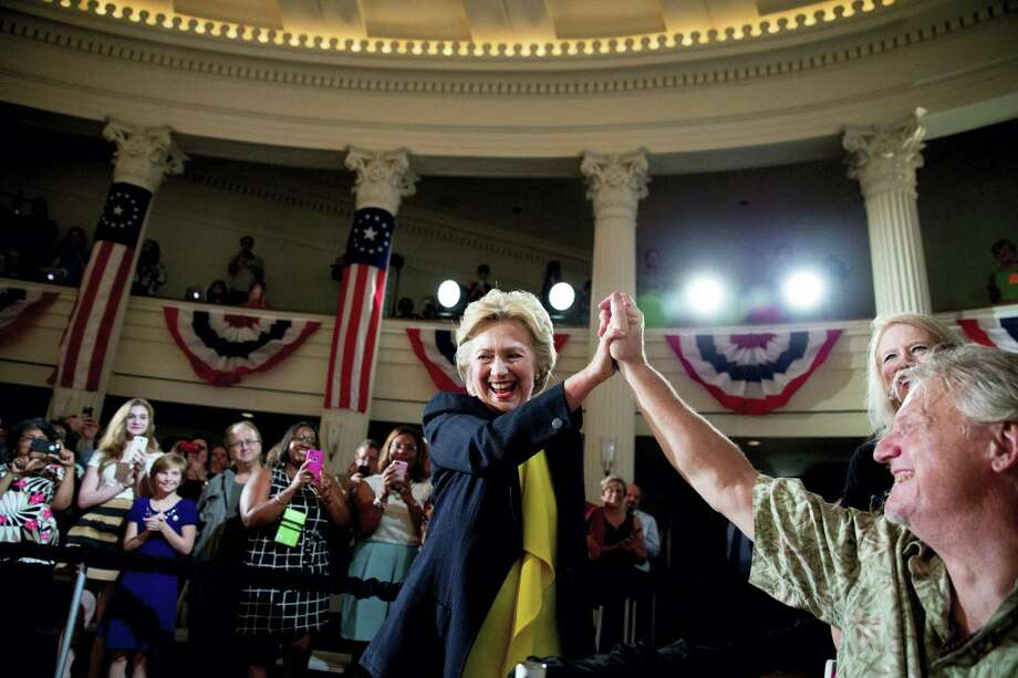 In this July 13, 2016 photo, Democratic presidential candidate Hillary Clinton high fives a member of the audience as she arrives to speak at the Old State House in Springfield, Ill. Clinton's campaign is launching a major voter mobilization drive during the Republican National Convention, setting a national goal of getting more than 3 million people to register and commit to vote in the 2016 election. Photo: AP Photo/Andrew Harnik, File  / Copyright 2016 The Associated Press. All rights reserved. This material may not be published, broadcast, rewritten or redistribu