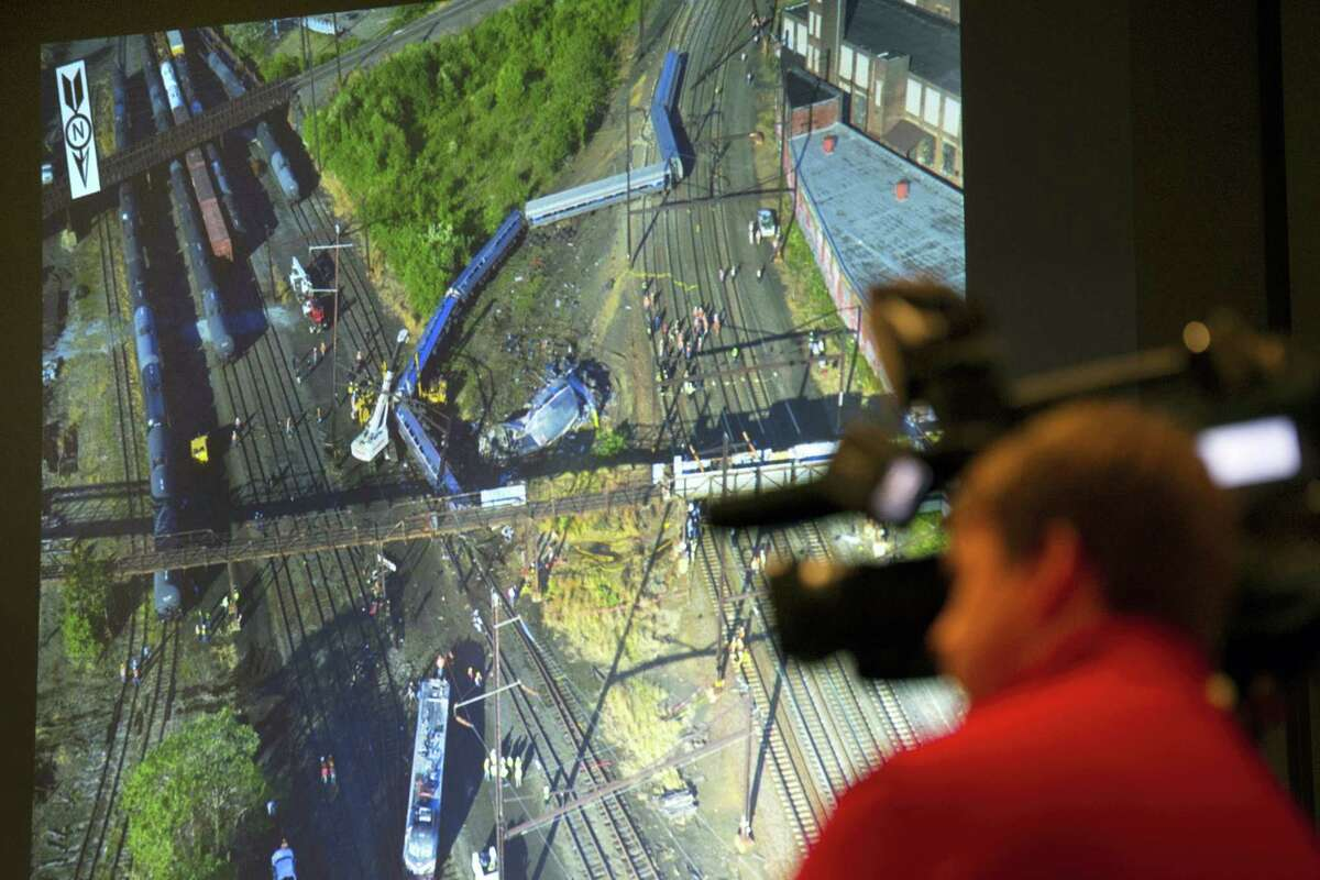 A photograph is displayed on a video monitor of the derailment of Amtrak passenger train in Philadelphia last year during a National Transportation Safety Board (NTSB) meeting on the derailment, Tuesday, May 17, 2016, in Washington.