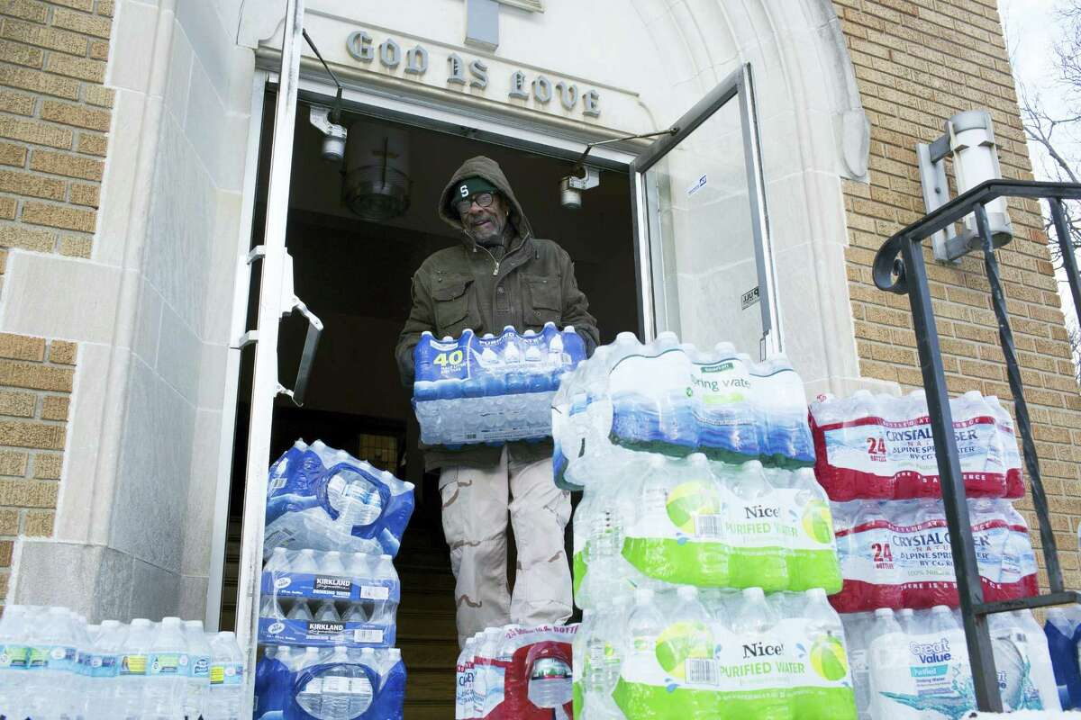 Maurice Rice organizes cases of water at the Joy Tabernacle Church on Monday, Jan. 11, 2016, in Flint, Mich. Michigan Gov. Rick Snyder pledged Monday that officials would make contact with every household in Flint to check whether residents have bottled water and a filter and want to be tested for lead exposure while his embattled administration works on a long-term solution to the city's water crisis.