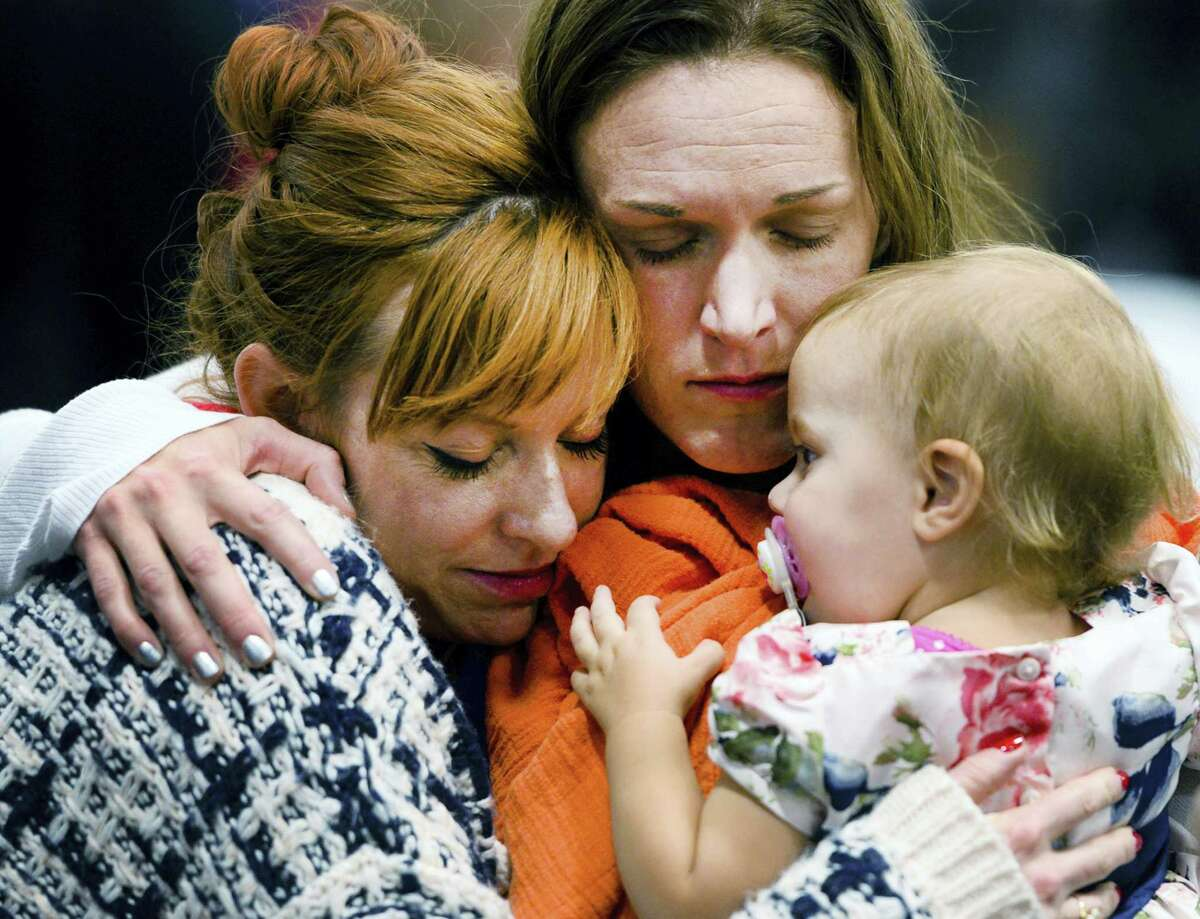 In this Dec. 19, 2015, file photo, Renee Wetzel, widow of Michael Wetzel, center, and her daughter Allie, are comforted by a woman during the memorial service for her husband at Calvary Chapel Conference Center in Twin Peaks, Calif. Wetzel the widow of Michael Wetzel, killed in last month's mass shooting in San Bernardino has filed four claims with the county and is seeking damages totaling $58 million, according to a newspaper report.