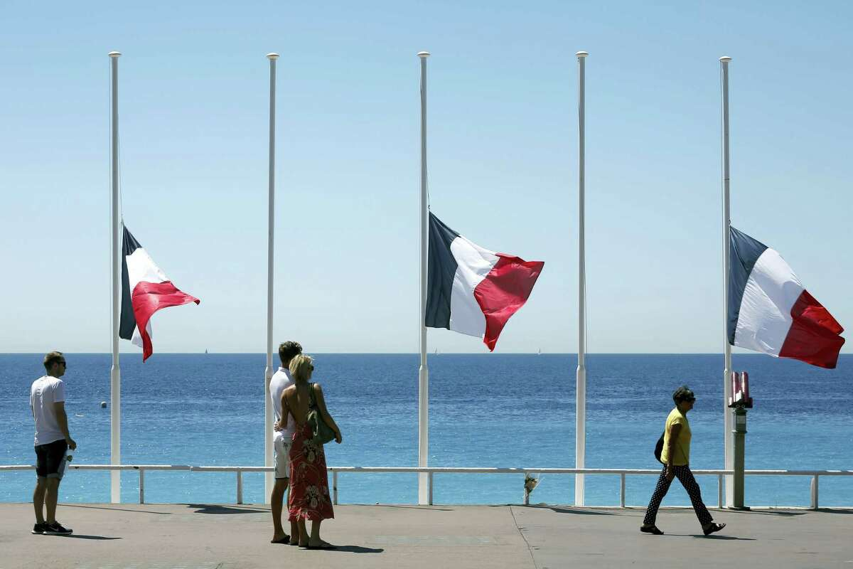 People stroll on the Promenade des Anglais with the French flag at half mast, near the scene of a truck attack in Nice, southern France, Saturday, July 16, 2016. The man responsible for turning a night of celebration into one of carnage in the seaside city of Nice was a petty criminal who hadn't been on the radar of French intelligence services before the attack.